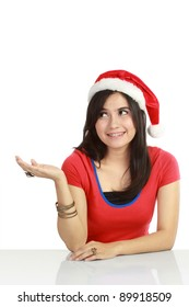 Christmas woman showing something with her hand. Isolated over white background