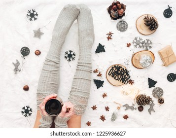 Christmas Woman's legs wearing warm socks .Cozy winter , cup of coffee, holiday concept