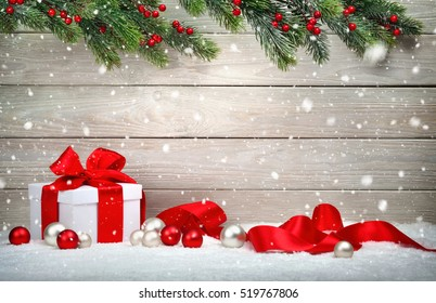 Christmas wood background with a white gift box, red bow and ribbon, baubles, fir branches and snow