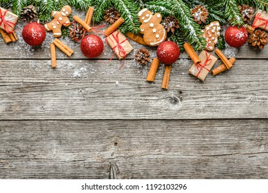 Christmas wooden background with fir branches, balls and other decorations, gingerbread cookies and rustic gift boxes, top view