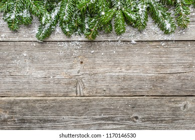 Christmas wooden background with fir and snow, holiday border