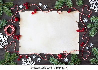 Christmas wooden background with paper, snowflakes, branches tree, red berries and twine in the form of hearts