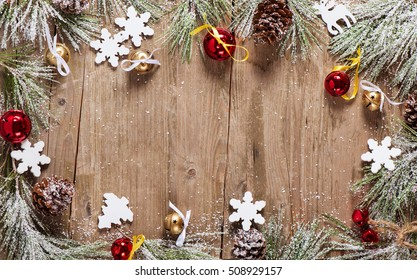 Christmas wooden background with snow, pine, cones and jingle bells.