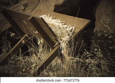 Christmas wooden manger with straws in it. Nativity manger near large rock boulders.