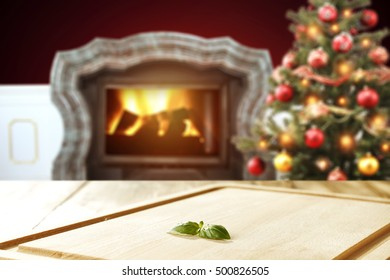 christmas wooden table of free space with background of fireplace and xmas tree in home