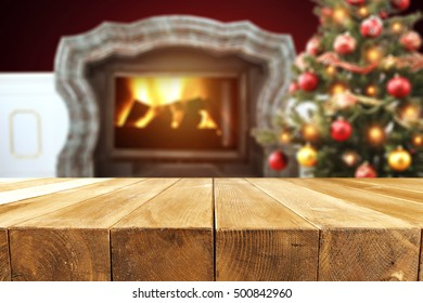 christmas wooden table place with background of xmas tree and fireplace