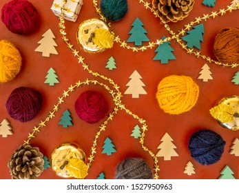 Christmas wool composition. Flat lay with balls of yarn, wooden christmas trees in green and white, gold colored decoration and pine cones. On a red background.