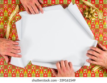 Christmas wrapped present being ripped open by four hands