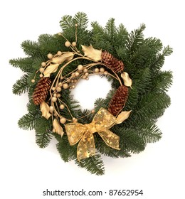 Christmas wreath of blue spruce fir with pine cones, golden holly, ribbon and balls isolated over white background.