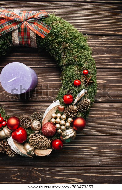 Christmas wreath and candle on a wooden background