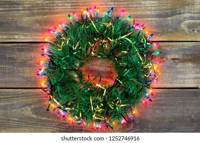 Christmas wreath with colorful ribbon and lights hanging on antique rustic wood door; seasonal holiday background