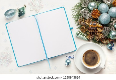 Christmas wreath, cup of coffee and Blank open notepad on white background. New year goals concept, mockup, top view, copy space