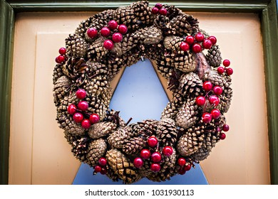 Christmas wreath decorated with fir cones and red berries on the door of the house in Europe