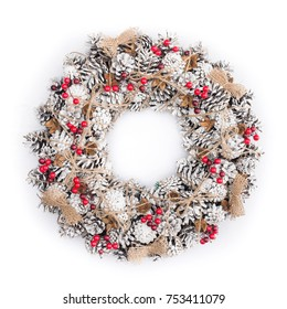 Christmas wreath decorated with pine cones, snow and red berries isolated on white, winter holidays background, top view