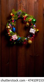 Christmas wreath decorated with toys on an old wooden brown door