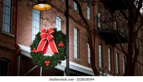 A Christmas wreath decoration hanging on a streetlamp in an urban setting.