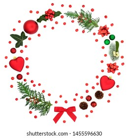 Christmas wreath decoration with loose holly berries, baubles, winter flora and symbols on white background with copy space. Festive concept for the holiday season.
