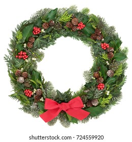Christmas wreath decoration with a red bow, holly, mistletoe, snow covered juniper fir, blue spruce, cedar, pine cones  and ivy leaves on white background.