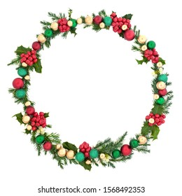 Christmas wreath decoration with winter flora and baubles on white background with copy space. Decorative symbol for the festive season.