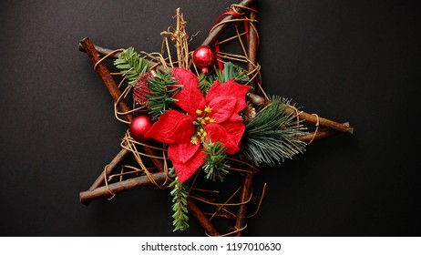 Christmas wreath with dry twigs, pine branches, red balls and poinsettia flower on wooden star shaped decoration isolated on black background. Flat lay. Top view.