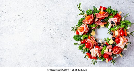 Christmas wreath of festive snacks. Cheese canapes with vegetables and ham. Christmas food wreath.