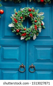 Christmas wreath of fir branches on a blue wooden door and a garland of fir branches.