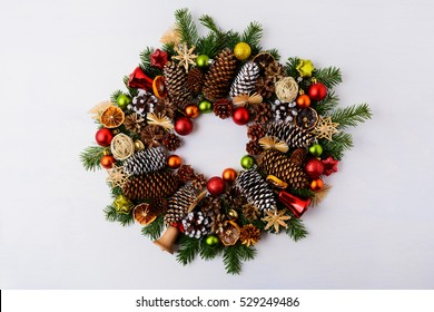 Christmas wreath with fir branches, pine cones and jingle bells. Christmas background with baubles, rustic ornaments and dried orange slices
