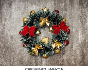 Christmas wreath of fir branches with fir tree balls on the concrete background. Top view. Holiday concept