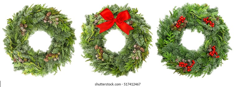 Christmas wreath from fir, pine and spruce twigs with cones, berries and ribbon bow isolated on white background