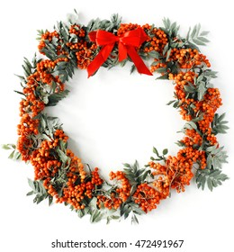 christmas wreath frame made of red rowan with bow on white background. flat lay, frame wreath, autumn wallpaper, christmas wallpaper
