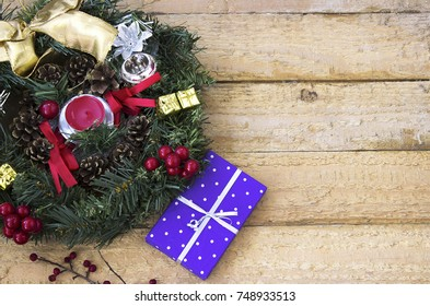 Christmas wreath and Christmas gift on a wooden surface - view from above