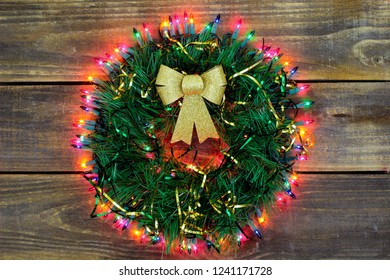 Christmas wreath with gold bow, ribbon and colorful lights hanging on antique rustic wood door; seasonal holiday background