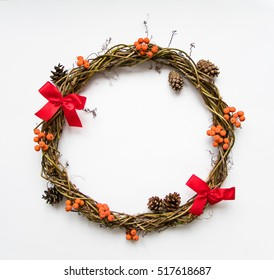 Christmas wreath of grape vines, decorated with red bows, rowanberries and cones. Festive DIY wreath. New Year round wreath on white background. Flat lay, top view