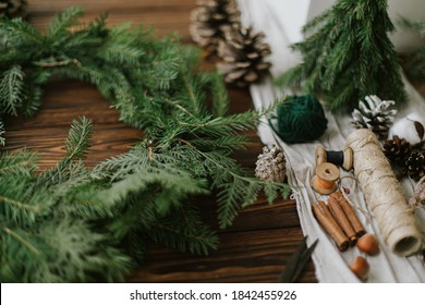 Christmas wreath with green branches, pine cones and natural festive decorations, scissors, twine. Making rustic christmas wreath on wooden table, seasonal holiday advent