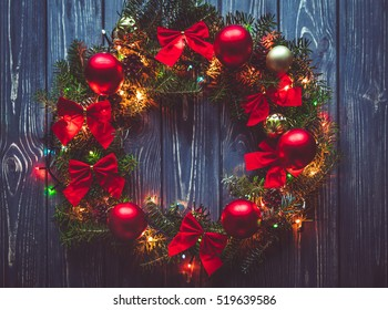 Christmas wreath handmade on a wooden background. Festive lights of garland. New Year's interior decoration
