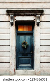 Christmas wreath hanging on a door of a house. Christmas branch with mandarines. The door is decorated for christmas
