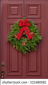Christmas wreath hanging on a red wooden door