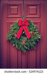 Christmas wreath hanging on a red wooden door. Vintage filter effects.
