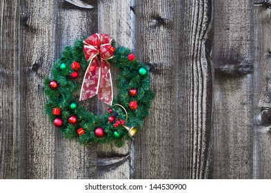 Christmas wreath hanging on rustic wooden fence