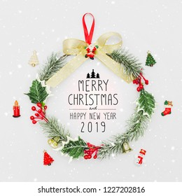 Christmas wreath and Happy New Year 2019 decorative ornament on white background with snow falling.Gifts and congratulations holidays concept.