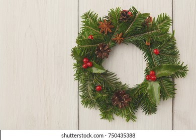 Christmas wreath with holly, pine cones and anise stars on white wooden door. Traditional design of winter welcoming decoration, new year background with copy space, closeup