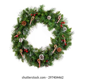 Christmas wreath isolated on white background. Decorated with candy canes, cones and red berries.