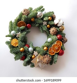 Christmas wreath lies on a white background. Decor elements are cones, glass balls, dried mugs of oranges, Christmas stars, cotton bolls. The basis of the wreath is spruce branches.