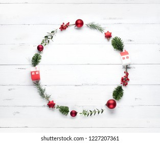 Christmas wreath made of fir branches, apple and berry on white background. Flat lay