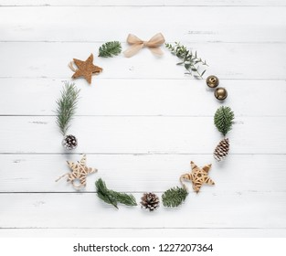 Christmas wreath made of fir branches, balls and pine cones on wooden background. Flat lay