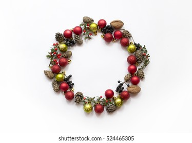 Christmas wreath made of toys, pine cones, nuts isolated on white background. Top view, flat lay.