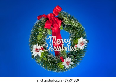 Christmas Wreath with Merry Christmas on a blue background with copy space.