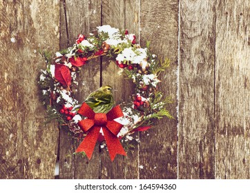 Christmas wreath with natural decorations with a beautiful male pine siskin bird perched, hanging on a rustic wooden wall with copy space.