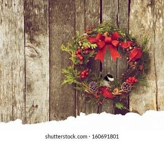 Christmas wreath with natural decorations, a big red bow,  and a cute little chickadee peeking out hanging on a rustic wooden wall with copy space.