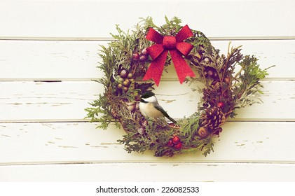 Christmas wreath with natural decorations hanging on a rustic wooden wall with a cute chickadee perched.